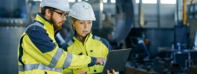 male-and-female-industrial-engineers-in-hard-hats-discuss-new-project-picture-id879813818