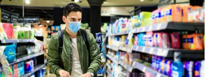 man-with-the-mask-on-his-face-at-the-supermarket-is-looking-for-a-picture-id1215769837
